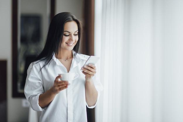 Retrato de uma linda menina morena feliz pela manhã com café e um telefone perto da janela.