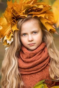 Retrato de uma linda menina nas folhas de outono