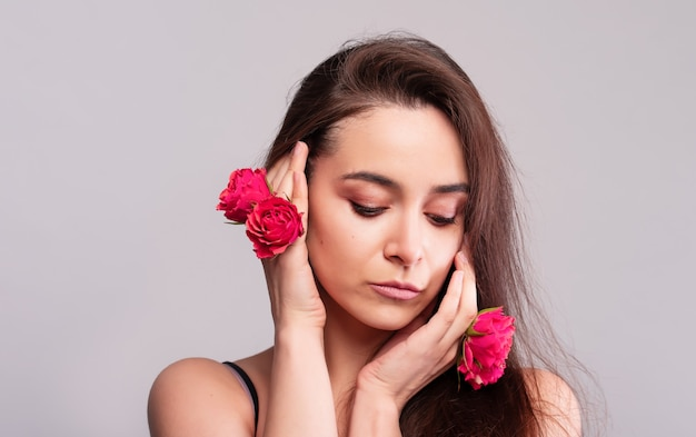 Retrato de uma linda menina natural de olhos azuis com flores vermelhas na natureza. maquiagem nua