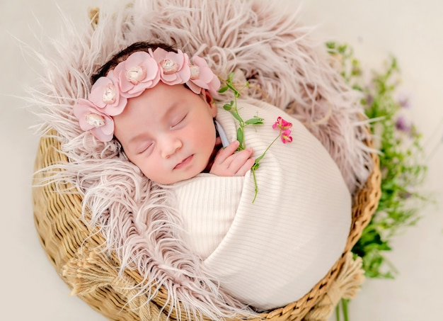 Retrato de uma linda menina recém-nascida envolta em tecido e usando uma grinalda com flores dormindo na cesta com peles durante a sessão de fotos de estúdio. criança fofa cochilando