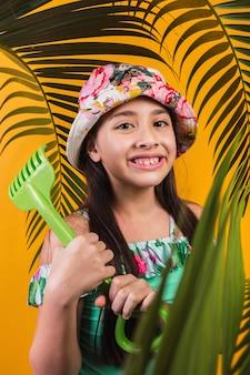 Retrato de uma linda menina segurando um raspador de plástico em um fundo amarelo.