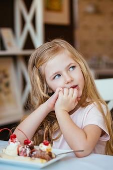 Retrato de uma linda menina sentada em um café à mesa de sonho com uma bola de sorvete com frutas.
