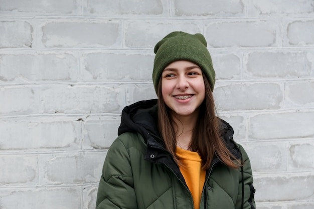 Retrato de uma linda menina sorridente com aparelho em um suéter amarelo e chapéu cáqui, que fica perto de uma parede de tijolos brancos. o conceito de emoções e espaço da cópia