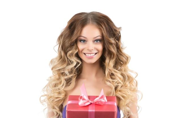 Retrato de uma linda menina sorridente com presentes em fundo branco. uma garota com lindos cabelos cacheados e maquiagem