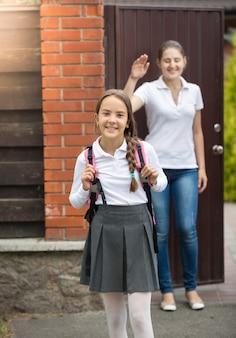 Retrato de uma linda menina sorridente com uma bolsa para ir para a escola