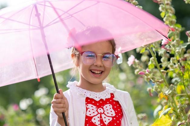 Retrato de uma linda menina sorridente de óculos, sob um guarda-chuva rosa