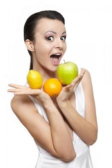 Retrato de uma linda menina sorridente feliz com frutas limão e maçã verde e laranja isolado no branco