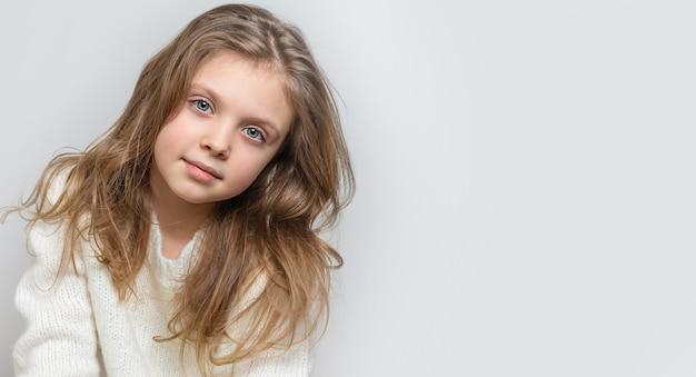 Retrato de uma linda menina sorridente feliz em um fundo branco, banner. copie o espaço para o texto