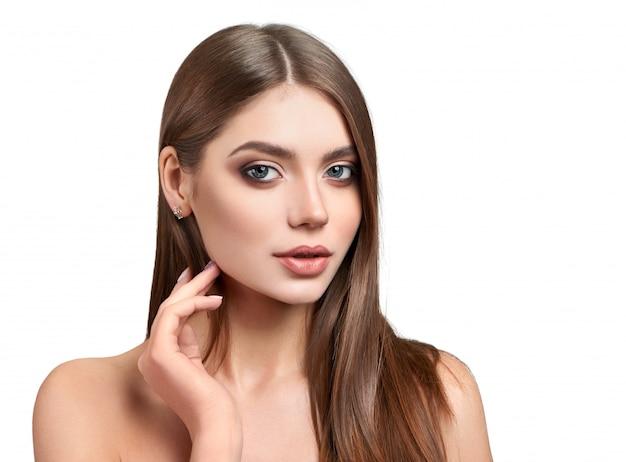 Retrato de uma linda modelo de olhos verdes com maquiagem, tocando seu queixo