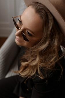 Retrato de uma linda modelo feminina com maquiagem perfeita, chapéu da moda e óculos de sol da moda