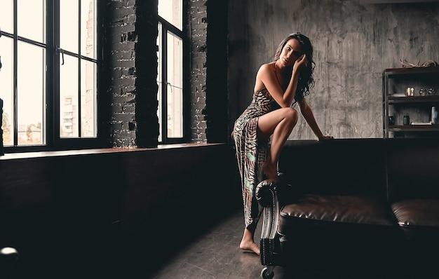 Retrato de uma linda morena deslumbrante com cabelos cacheados em um vestido que posa perto de um sofá de couro, mostrando pernas esguias.