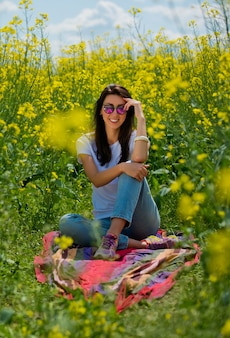 Retrato de uma linda morena em óculos de sol, senta-se no campo de colza. tiro vertical.