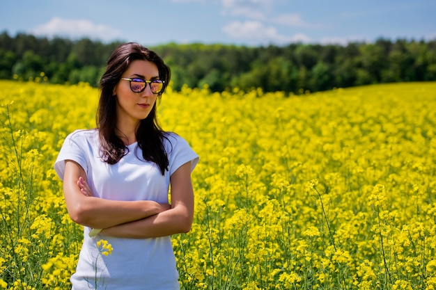Retrato de uma linda morena em óculos de sol, senta-se no campo de colza.