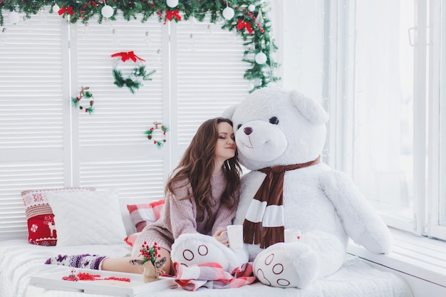 Retrato de uma linda mulher abraçando o ursinho de pelúcia na sala de natal