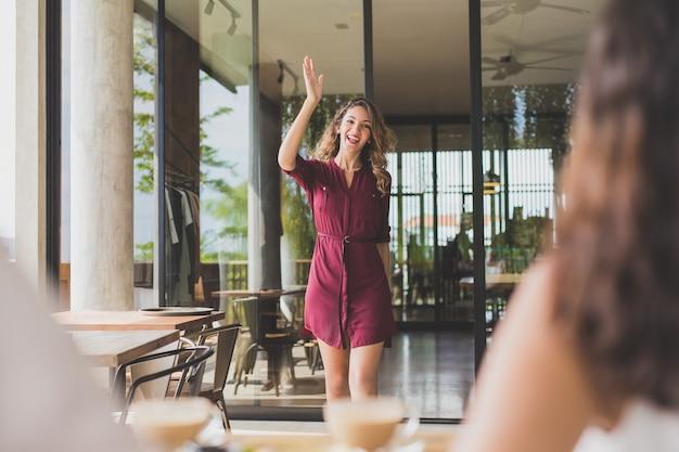 Retrato de uma linda mulher acenando com as mãos para as amigas enquanto caminhava até elas