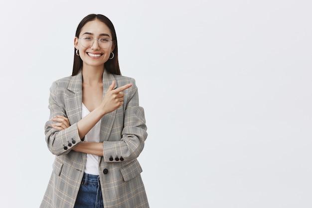 Retrato de uma linda mulher adulta despreocupada de óculos e jaqueta sobre camiseta branca, apontando para o canto superior direito e sorrindo com dentes brilhantes