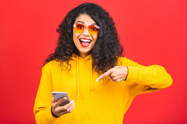 Retrato de uma linda mulher afro-americana com óculos de sol usando telefone