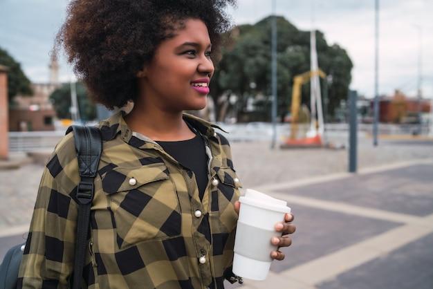 Retrato de uma linda mulher afro-americana do latim segurando uma xícara de café ao ar livre na rua. conceito urbano.