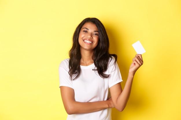 Retrato de uma linda mulher afro-americana em camiseta branca sorrindo satisfeito e mostrando cartão de crédito