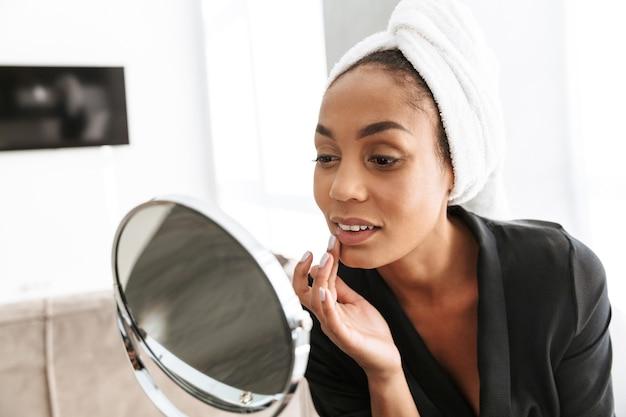 Retrato de uma linda mulher afro-americana em roupão, enrolada em uma toalha branca, aplicando creme facial contra o espelho