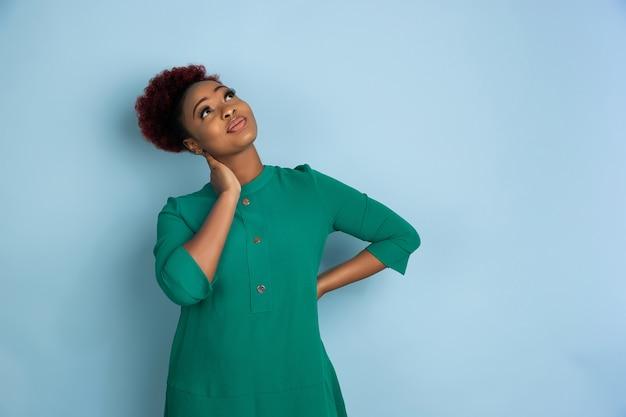 Retrato de uma linda mulher afro-americana na parede azul