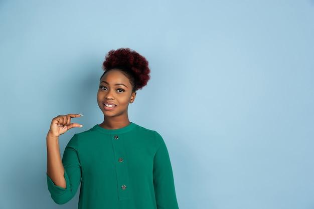 Retrato de uma linda mulher afro-americana no fundo azul do estúdio