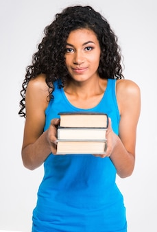 Retrato de uma linda mulher afro-americana segurando livros isolados em uma parede branca