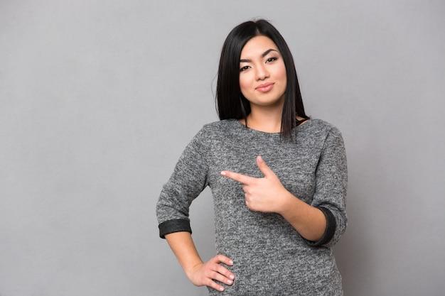 Retrato de uma linda mulher apontando o dedo na parede cinza