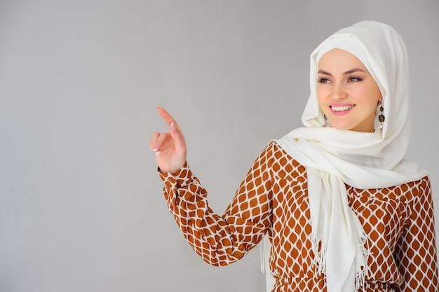 Retrato de uma linda mulher árabe com lenço na cabeça apontando o dedo para o espaço da cópia
