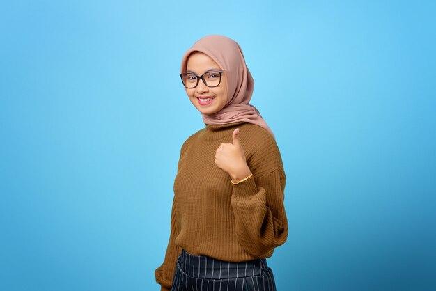 Retrato de uma linda mulher asiática alegre mostrando os polegares sobre fundo azul