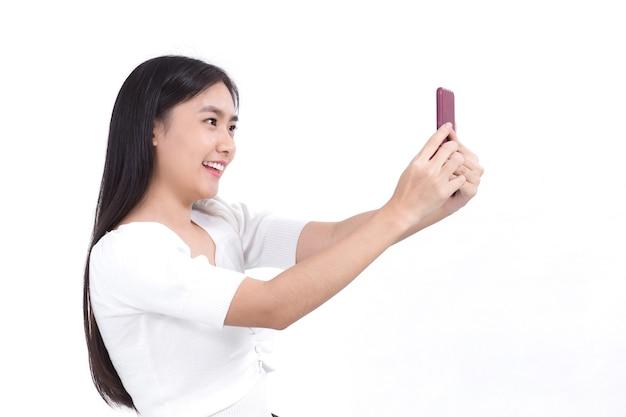 Retrato de uma linda mulher asiática com cabelo comprido preto e camisa branca segurando o smartphone