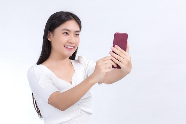 Retrato de uma linda mulher asiática com cabelo comprido preto em uma camisa branca segurando o smartphone