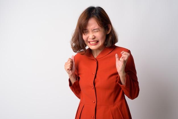 Retrato de uma linda mulher asiática com cabelo curto contra uma parede branca