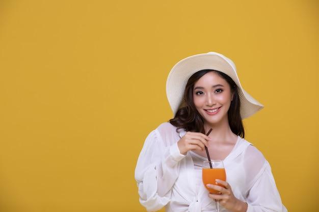 Retrato de uma linda mulher asiática com chapéu segurando um copo de suco de laranja