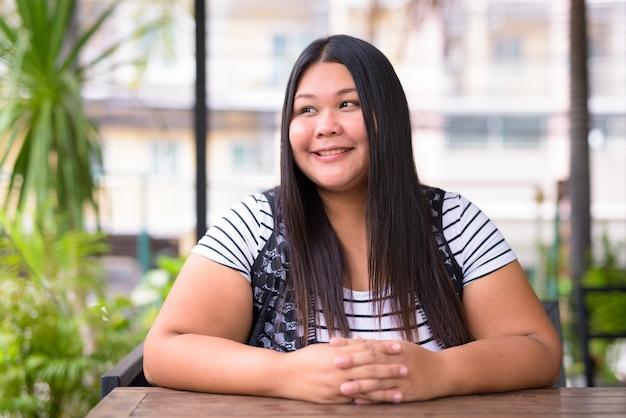 Retrato de uma linda mulher asiática com excesso de peso relaxando em uma cafeteria