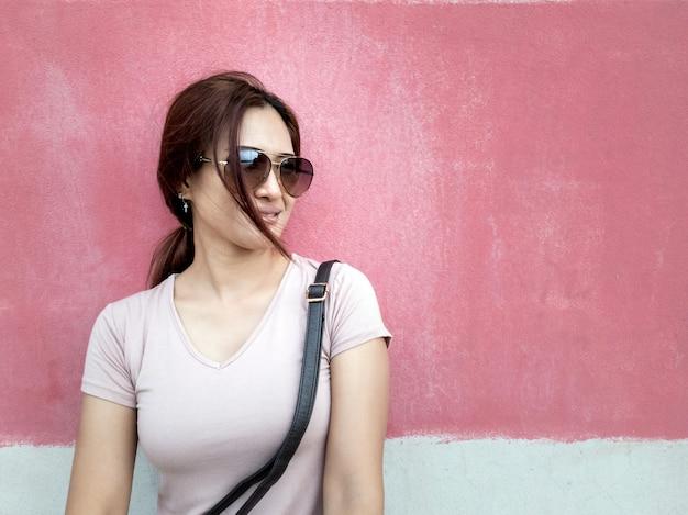 Retrato de uma linda mulher asiática com óculos de sol em uma cidade ao longo do fundo da parede rosa
