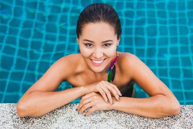 Retrato de uma linda mulher asiática em maiô preto, banhando-se na piscina do spa de luxo, usando um brinco de pena sorridente, sexy, corpo bronzeado magro e pele molhada, acessórios de estilo de verão,