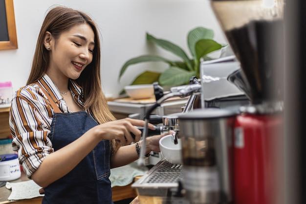 Retrato de uma linda mulher asiática em um avental usando uma máquina de café, ela é dona de uma cafeteria, conceito de uma empresa de alimentos e bebidas. gestão de loja por uma mulher de negócios.