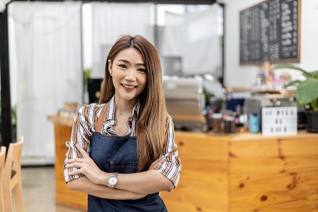 Retrato de uma linda mulher asiática em um pé de avental em uma cafeteria, ela é proprietária de uma cafeteria, o conceito de uma empresa de alimentos e bebidas. gestão de loja por uma mulher de negócios.
