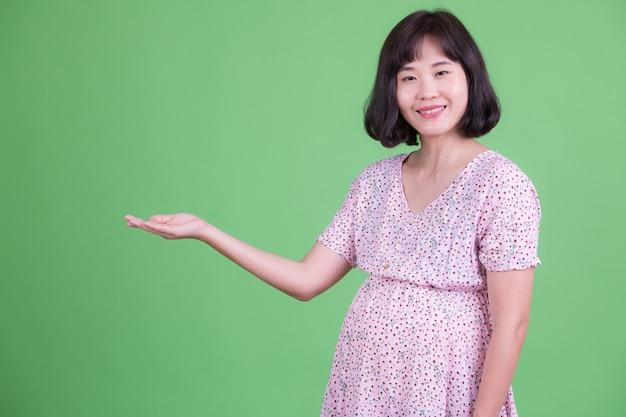 Retrato de uma linda mulher asiática grávida com cabelo curto contra chroma key ou parede verde