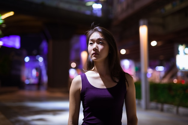 Retrato de uma linda mulher asiática pensando ao ar livre à noite