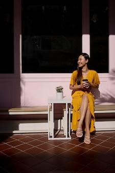 Retrato de uma linda mulher asiática posando ao ar livre com um vestido amarelo