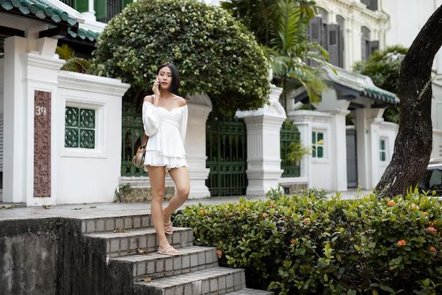 Retrato de uma linda mulher asiática posando ao ar livre em um vestido branco