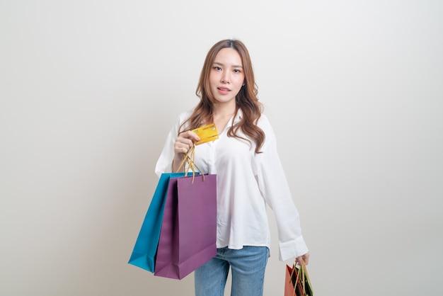 Retrato de uma linda mulher asiática segurando uma sacola de compras e um cartão de crédito no fundo branco