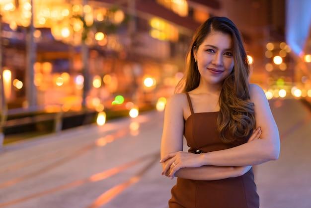 Retrato de uma linda mulher asiática sorrindo ao ar livre em bangkok, tailândia, à noite