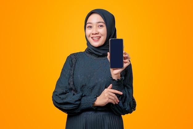 Retrato de uma linda mulher asiática sorrindo e segurando com tela preta vazia,