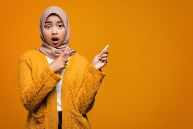 Retrato de uma linda mulher asiática surpreso e apontando com o dedo para o espaço vazio