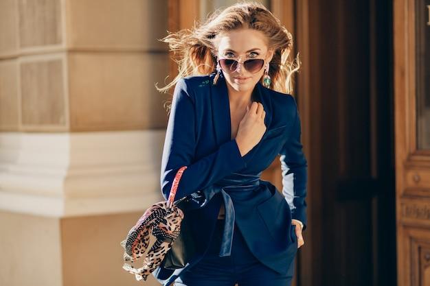 Retrato de uma linda mulher atraente e sorridente, vestida com um elegante terno azul, caminhando pela cidade
