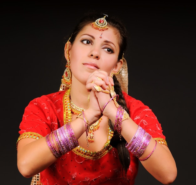 Retrato de uma linda mulher branca branca em traje tradicional indiano, entrelaçando os dedos em um fundo escuro