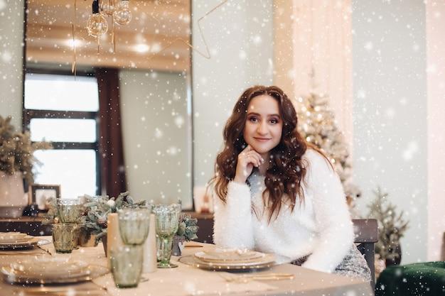 Retrato de uma linda mulher branca com cabelo escuro sentado na grande cozinha bem iluminada